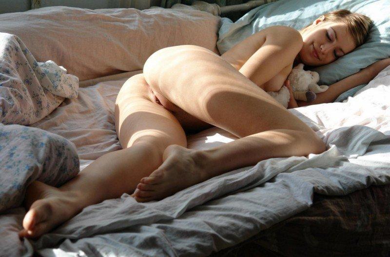 Спящая голышом красавица с любимой мягкой игрушкой в обнимку.