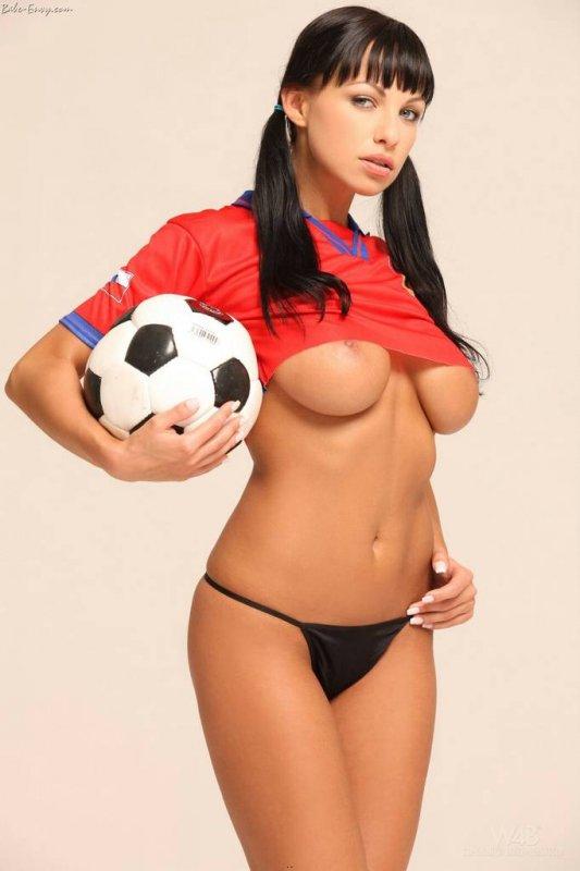 Брюнетка в футболке спортивного клуба и три мячика - один в руках и два под футболкой.